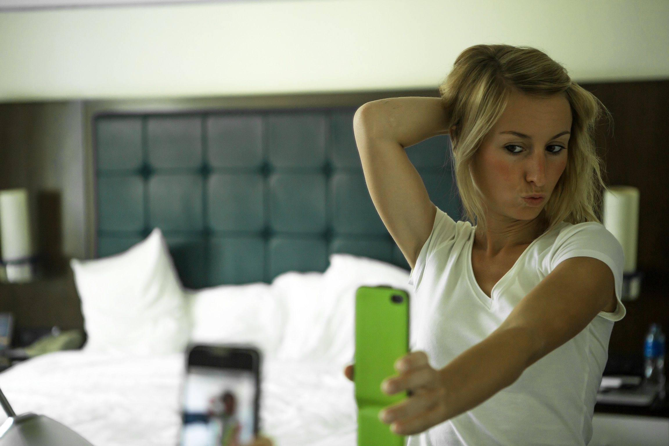 Young woman in an hotel room taking a selfie in the morning, sunlight coming in the room. She is taking a self portrait from the reflection in the mirror using her mobile phone.
